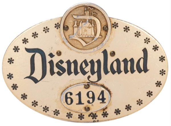 """An early Disneyland cast member pin, is estimated at $1,000-2,000. This rarity measures 2 ½"""" long, dates from the 1950s, is numbered 6194, and has a unique oval design."""