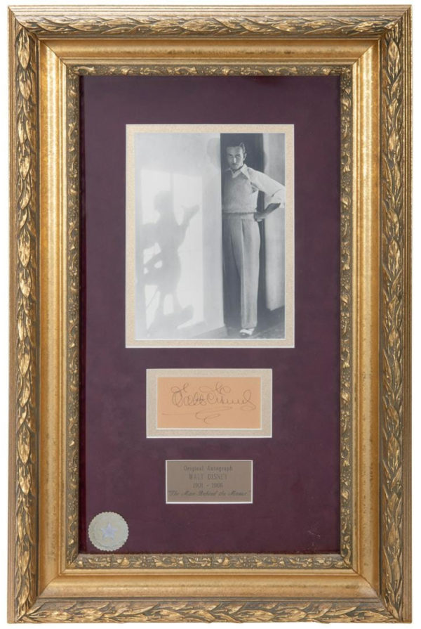 """Walt Disney autograph display, is estimated at $800-1,200. This 27-½ x 18"""" piece includes a clipped signature, a photo, and a plaque. It has a CoA from Walt Disney World Co. affixed to the back of its frame."""