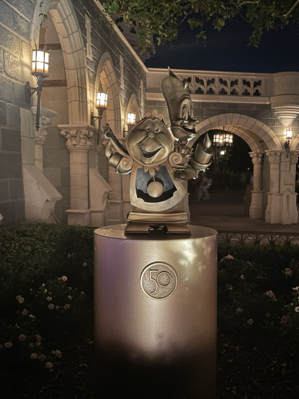 """Lumiere (16) and Cogsworth (17) in their """"cursed"""" versions appear in Fantasyland."""