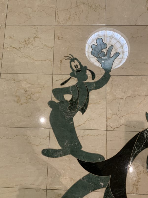 Goofy in the tile on the second floor as you enter the hotel from the monorail.
