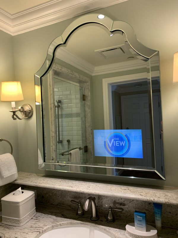 The bathroom mirror has a television in the mirror!
