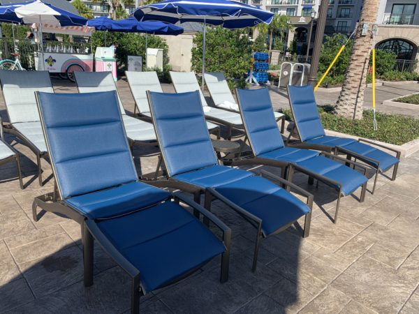 There are bold, blue lounge chairs sun umbrellas.