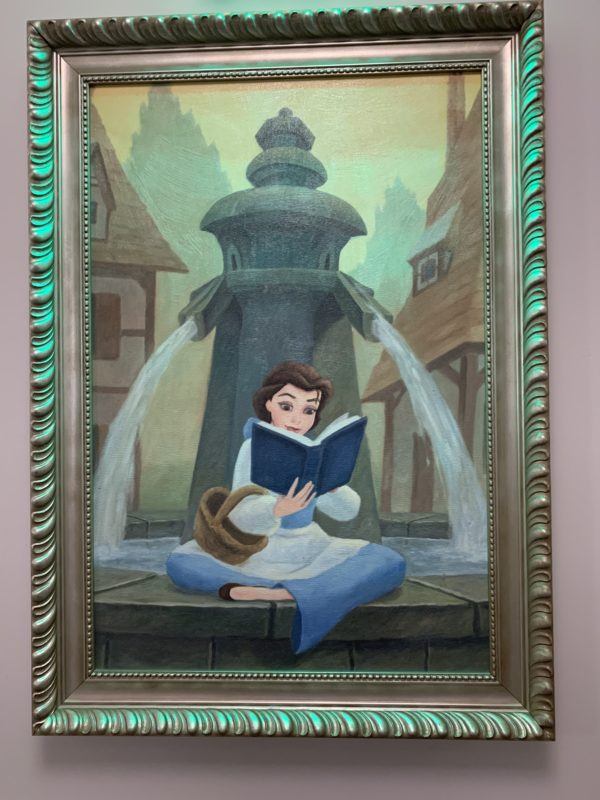 Here's Belle reading a book in front of a water fountain. Beauty and the Beast was inspired by the French countryside, which fits right in with the styling of this resort!