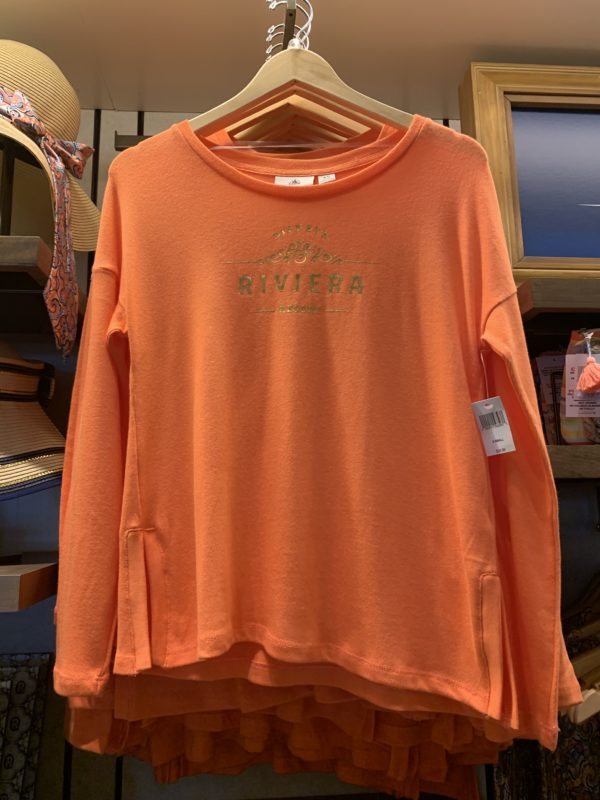 "This simple long-sleeve shirt has gold ""Disney's Riviera Resort"" writing."