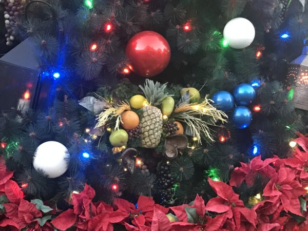 The ornaments on the Christmas tree features fruit including pineapples.