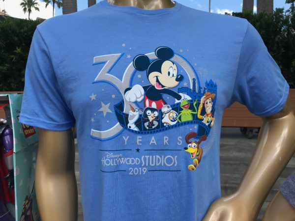 The t-shirt features Mickey Mouse and other characters you will see around the park.