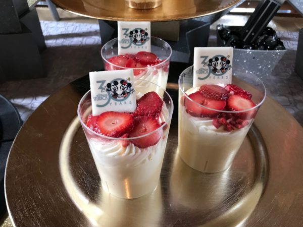 The tres leches cake is topped with whipped cream, fresh strawberry, strawberry candy, and a white chocolate 30th anniversary logo.
