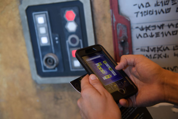 Use your smartphone as a data pad via MyDisneyExperience to translate the written language of Aurebesh and speak Batuuan!