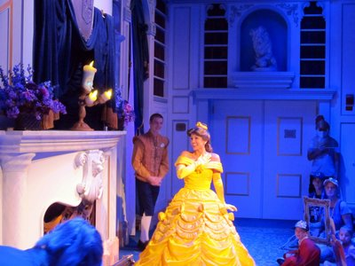 Belle in the library with Lumiere.