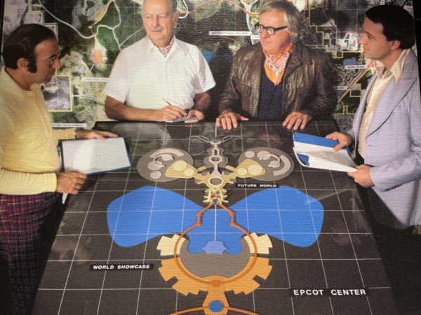 EPCOT designers Marty Sklar, John Hench, Ray Bradbury, and John DeCuir, Jr. examine an early concept for the future theme park. Photo credits (C) Disney Enterprises, Inc. All Rights Reserved