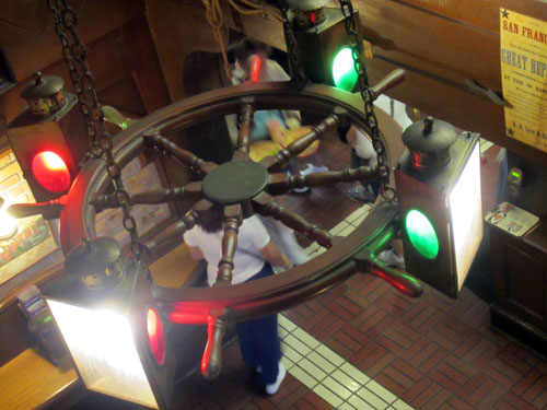 Ship's wheel turned into a huge light fixture.