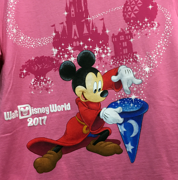 Sorcer Mickey throws some magic in his hat on this pink shirt with Animal Kingdom, Magic Kingdom, Hollywood Studios, and Epcot icons pictured in the background.