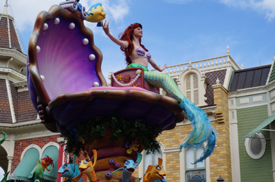 The Little Mermaid waves from high atop a shell.
