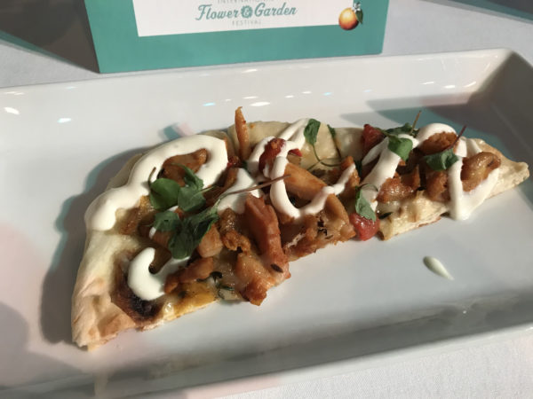 Honey Tandoori Chicken Flatbread with white cheddar cheese, charred vegetables, clover honey sour cream, and micro watercress