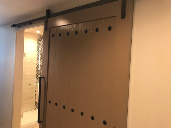 The bathroom is behind a trendy sliding barn door.