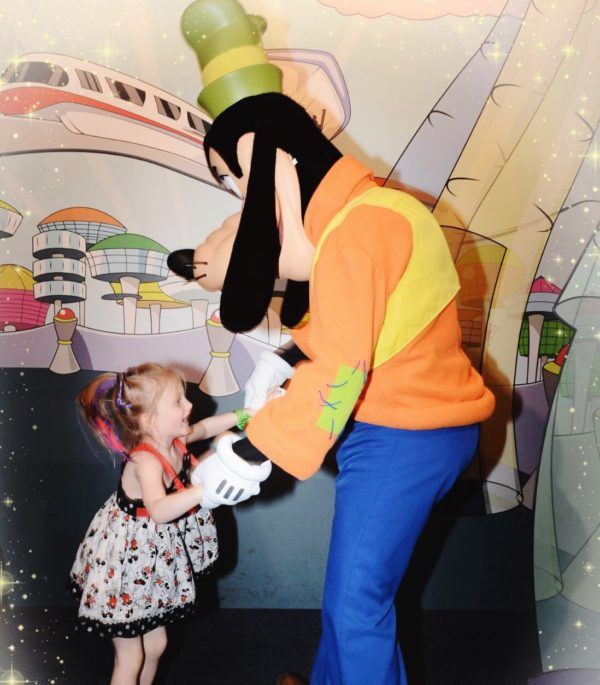 Our daughter, Hailey, living in the moment and dancing with Goofy.