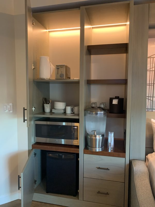 The kitchenette has lots of shelving, a mini fridge, a microwave, a toaster, some dishes, and your ice bucket.