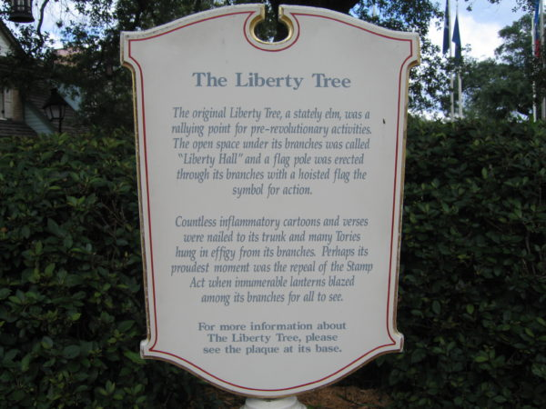 "The history of the liberty tree: The original Liberty Tree, a stately elm, was a rallying point for pre-revolutionary activities. The open space under its branches was called ""Liberty Hall"" and a flag pole was erected through its branches with a hoisted flag the symbol for action. Countless inflammatory cartoons and verses were nailed to its trunk and many Torries hung in effigy from its branches. Perhaps its proudest moment was the repeal of the Stamp Act when innumerable lanterns blazed among its branches for all to see."