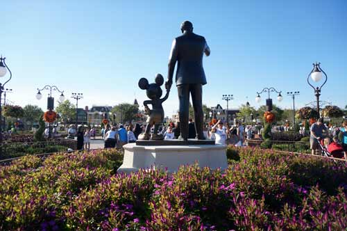 Beautiful purple flowers surround the Partners Statue with Walt and Mickey.
