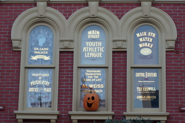 Walker's window on the far left above the Emporium recognizes his ability to mediate conflicts and manage personalities within the business and his love for golf in his personal life.