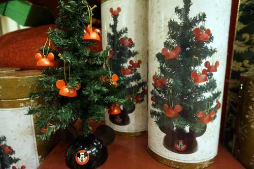 This Mickey-themed Christmas tree in a tube comes complete with tree, mouse-ears stand, and mouse ear decorations.