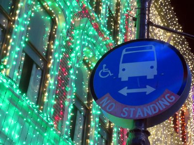 The bus sign says no standing, but there are plenty of folks standing around looking at the lights.