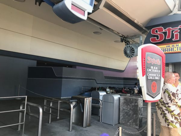 The wall in front of the Stitch attraction is dark at the bottom and white at the top.