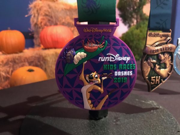 "Timon serves up some grubs on this runDisney Kids Races Dashes ""medal""."