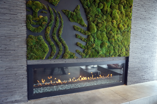 Small patio features a fireplace and art made from moss.