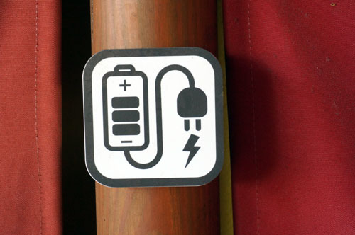 There are a few charging stations along the wall.  Look for this symbol.