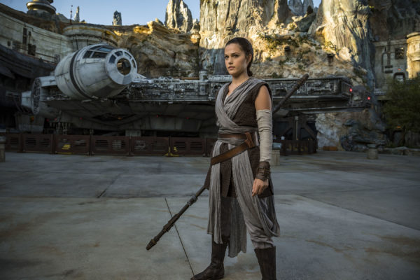 Heroine of the most recent Star Wars trilogy, Rey, standing in front of the Millennium Falcon. Photo credits (C) Disney Enterprises, Inc. All Rights Reserved