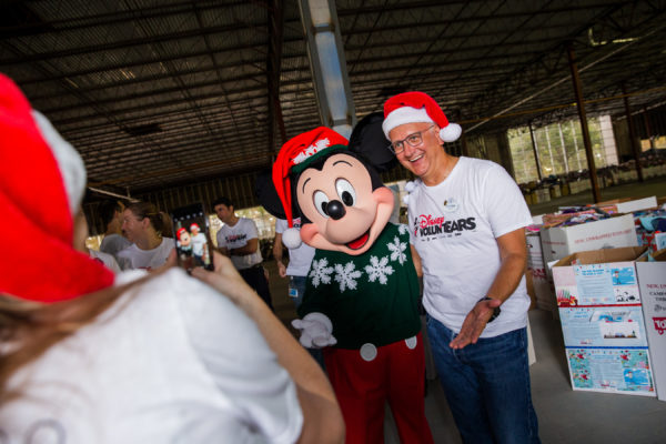 Toys for Tots VoluntEAR poses with Mickey Mouse