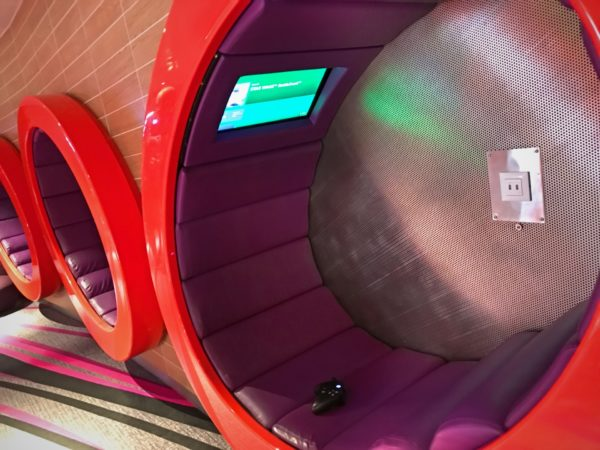 Check out these cool seats! They're mounted to the wall and feature a personal screen for game play.